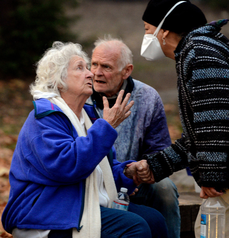 . Denise Gant, right, wears a face mask as she greets fellow Big Sur residents Clovis Harrod, left, and Grady Cook as firefighters battle a wildland fire in the Pfeiffer Ridge area in Big Sur on Monday December 16, 2013. (Photo David Royal/ Monterey County Herald)
