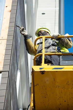 01/02/19 Wesley Bunnell | StaffrrA worker from Ultimate Construction LLC seals the newly installed outside siding on the third floor of Columbus Commons on Thursday afternoon.