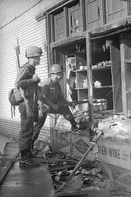 . Ohio National Guard lieutenants Robert Landus, left, of Mentor, Ohio, and John Ault of Hudson, Ohio, check a burned-out store in the Hough area in Cleveland, Ohio, July 20, 1966. The soldiers moved in at midnight after two days of shooting, burning and looting, and are patrolling the area in jeeps, trucks and on foot. They are armed with rifles and machine guns. (AP Photo/Julian C. Wilson)