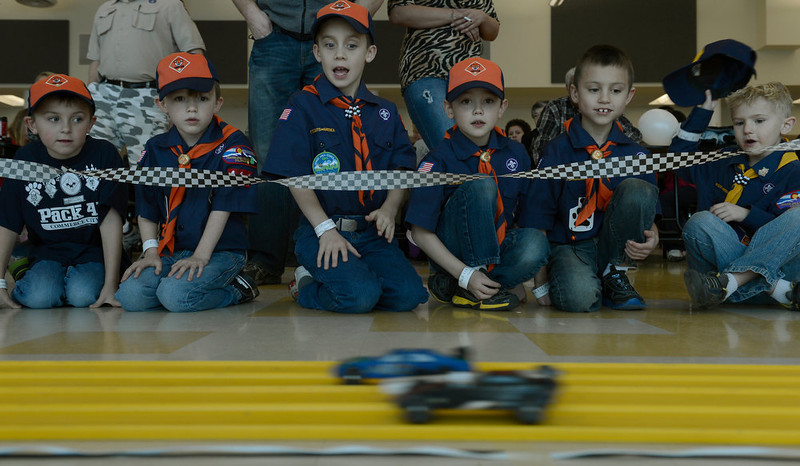 . COMMERCE CITY, CO. - JANUARY 26: Contestants line the track to watch the pinewood cars race by during the 2013 Pack 414 Pinewood Derby races at Ortho Stuart Middle School January 26, 2013 in Commerce City. The pinewood cars weigh 5 oz and are 7 inches long. The cars take about 3 second to go down the track.  The scouts can either buy a kit with the car already shaped or buy a block of wood and carve their own.  (Photo By John Leyba / The Denver Post)