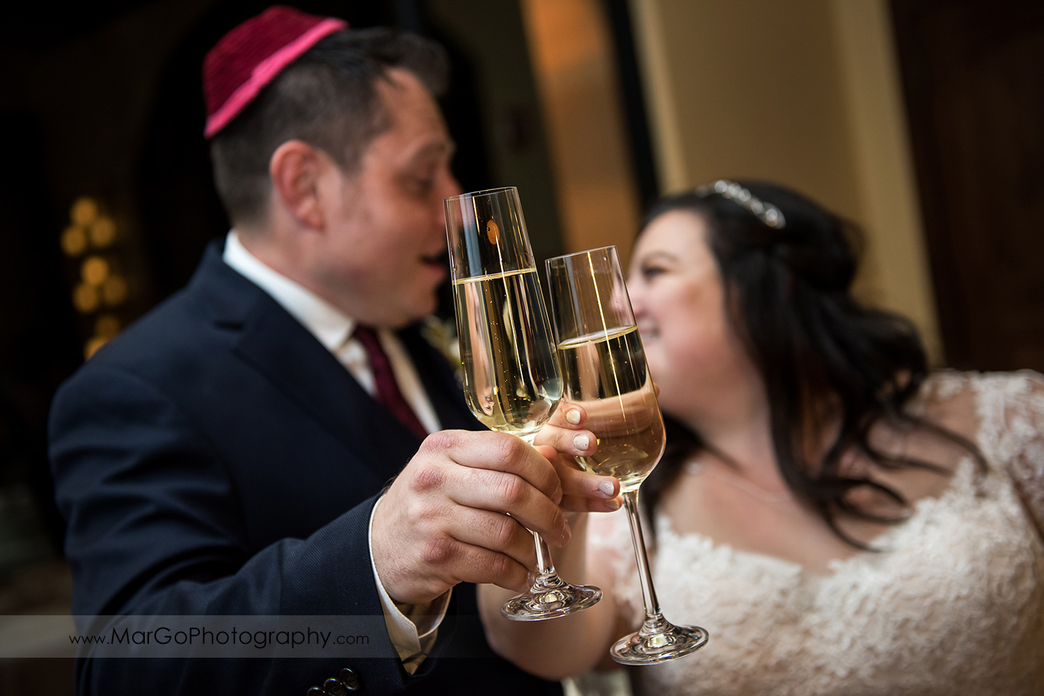 jewish bride and groom holding champagne glasses during wedding reception at Livermore Garre Vineyard and Winery