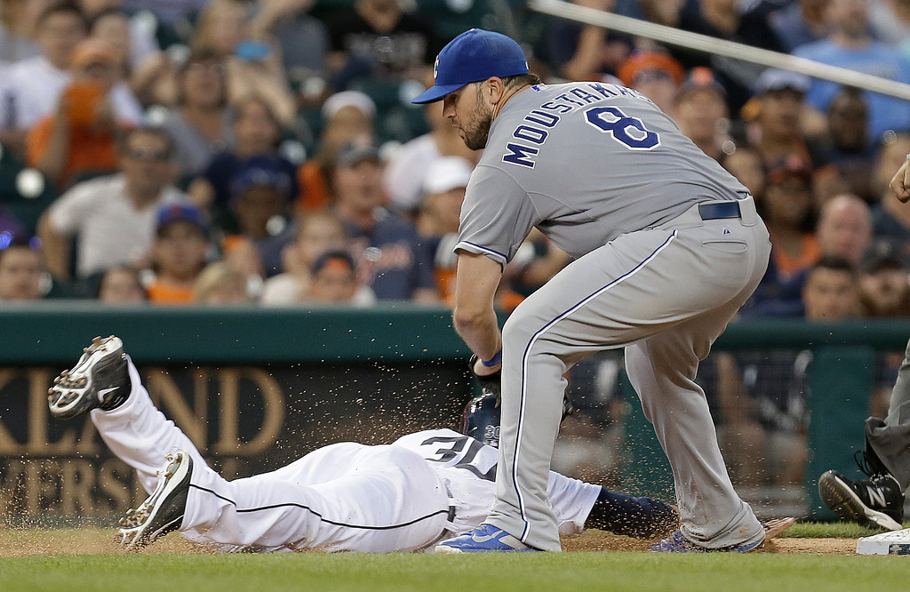 . Kansas City Royals third baseman Mike Moustakas (8) tags Detroit Tigers\' Eugenio Suarez out sliding back into third base in the fifth inning of a baseball game in Detroit, Tuesday, June 17, 2014.  (AP Photo/Paul Sancya)