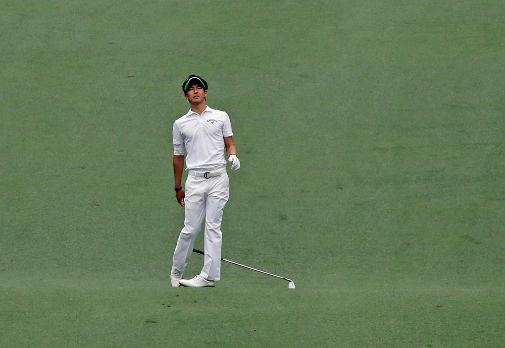 Description of . Ryo Ishikawa, of Japan, reacts his second shot on the seventh hole during the fourth round of the Masters golf tournament Sunday, April 14, 2013, in Augusta, Ga. (AP Photo/David J. Phillip)