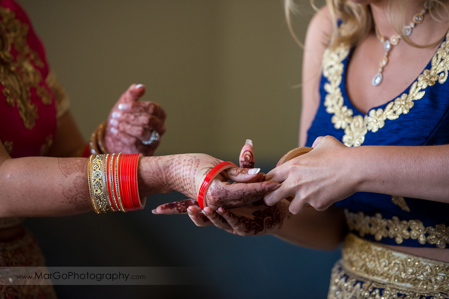 Indian bride preparation - putting on red and golden wedding bangles choora