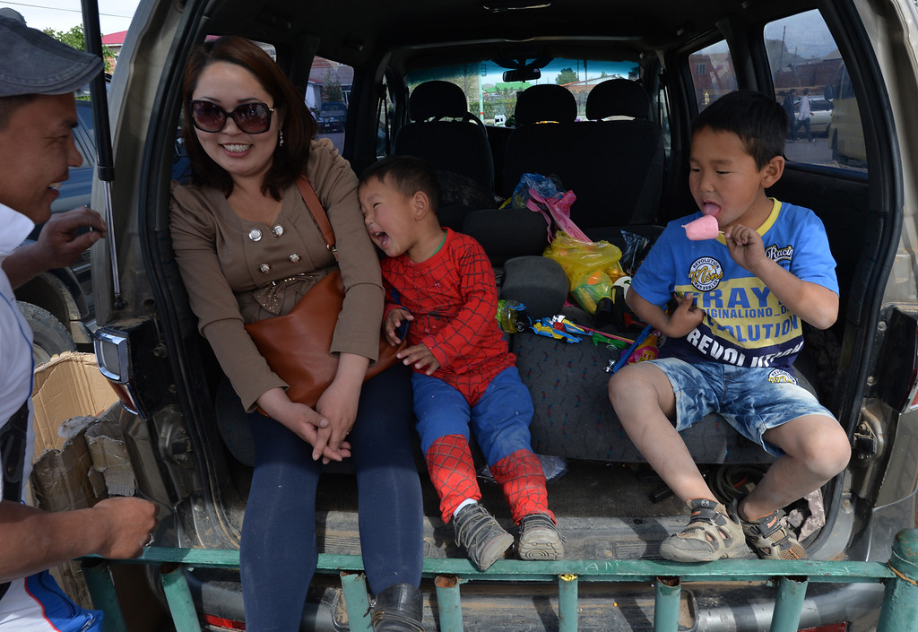 . A Mongolian family attends a carnival to celebrate International Children\'s Day at the Mongolian town of Bayangol on June 1, 2013.  Mongolia, along with current and former Communist countries, celebrates their Children\'s Day on June 1. MARK RALSTON/AFP/Getty Images