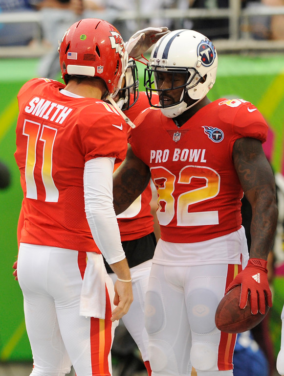 . AFC quarterback Alex Smith (11), of the Kansas City Chiefs, congratulates, tight end Delanie Walker (82), of the Tennessee Titans, after Walker scored a touchdown, during the second half of the NFL Pro Bowl football game against the NFC, Sunday, Jan. 28, 2018, in Orlando, Fla. (AP Photo/Steve Nesius)