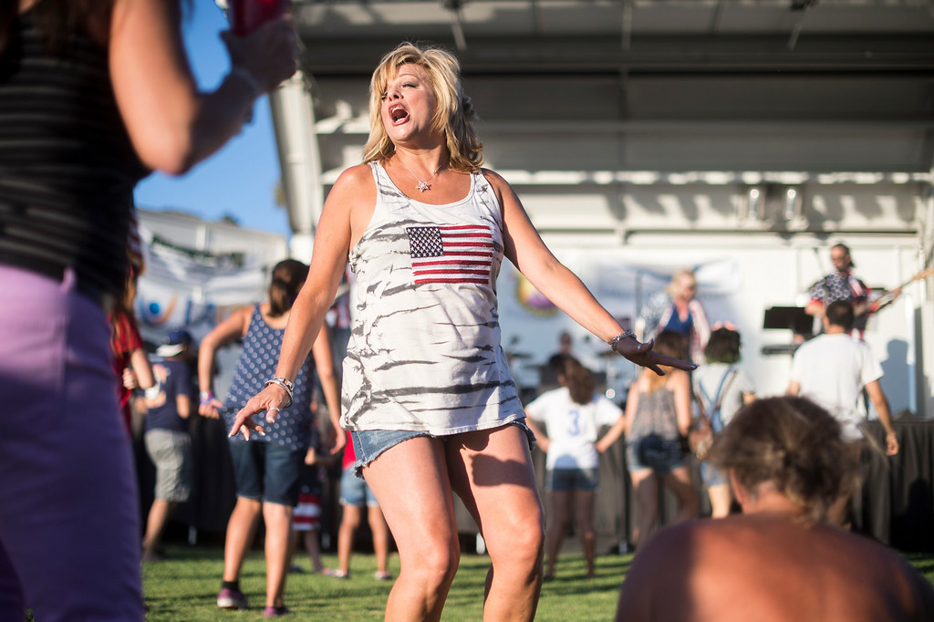. Wendy Fonzeca, who graduated from La Mirada High School in 1983, dances with high school friends to Yard Sale as La Mirada holds their annual fireworks show and festival Thursday night, July 3, 2014 at La Mirada Regional Park. (Photo by Sarah Reingewirtz/Pasadena Star-News)