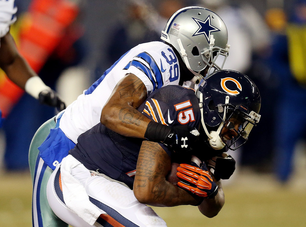 . Wide receiver Brandon Marshall #15 of the Chicago Bears is tackled by cornerback Brandon Carr #39 of the Dallas Cowboys during a game at Soldier Field on December 9, 2013 in Chicago, Illinois.  (Photo by Jonathan Daniel/Getty Images)
