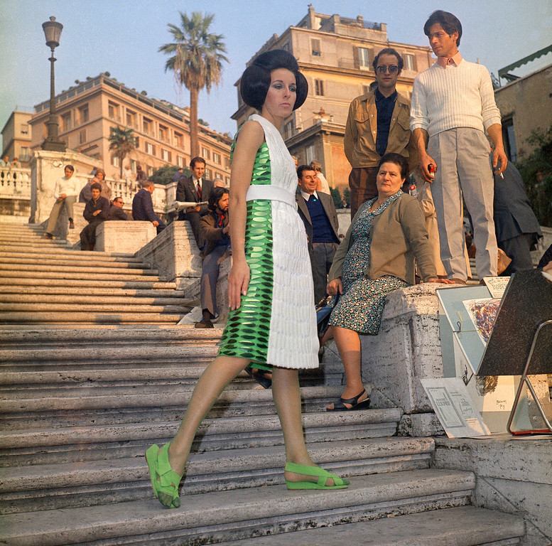 . Surrounded by hippies and young admires on the famed Spanish Steps in the center of Rome, Nov. 3, 1969, a fashion model presents an evening dress with oriental in-spried embroidery on green and white Linen, to be presented at the Florence show of Italian spring-summer 1970 high fashion ready-to-wear boutique collections, opening on November 3. (AP Photo/Mario Torrisi)