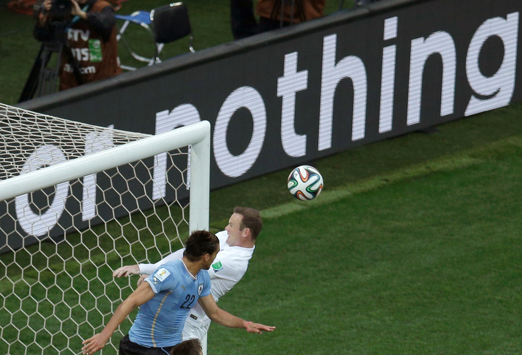 . England\'s Wayne Rooney, right, heads the ball against the crossbar as Uruguay\'s Martin Caceres looks on during the group D World Cup soccer match between Uruguay and England at the Itaquerao Stadium in Sao Paulo, Brazil, Thursday, June 19, 2014.  (AP Photo/Michael Sohn)