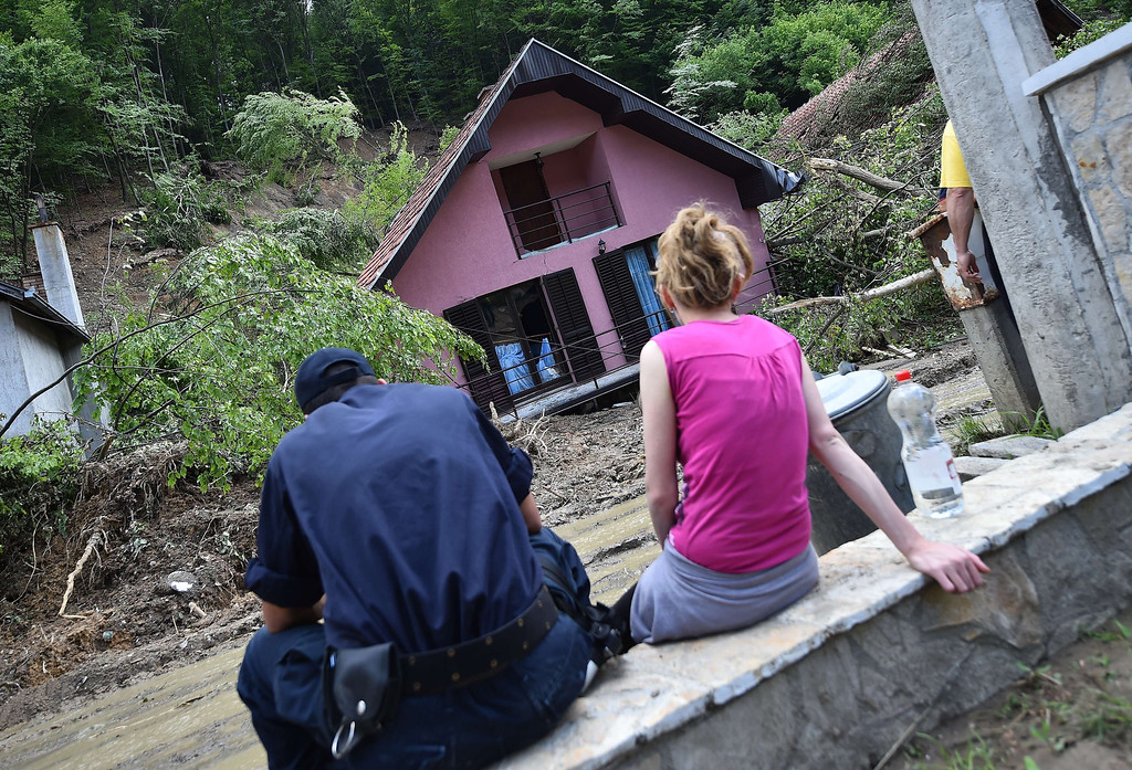 . A couple looks at their house damaged by flooding and landslides in Krupanj, some 130 kilometers south west of Belgrade, on May 20, 2014, after the western Serbian town was hit with floods and landslides, cutting it off for four days. Serbia declared three days of national mourning on May 20 as the death toll from the worst flood to hit the Balkans in living memory rose and health officials warned of a possible epidemic.    AFP PHOTO / ANDREJ  ISAKOVIC/AFP/Getty Images