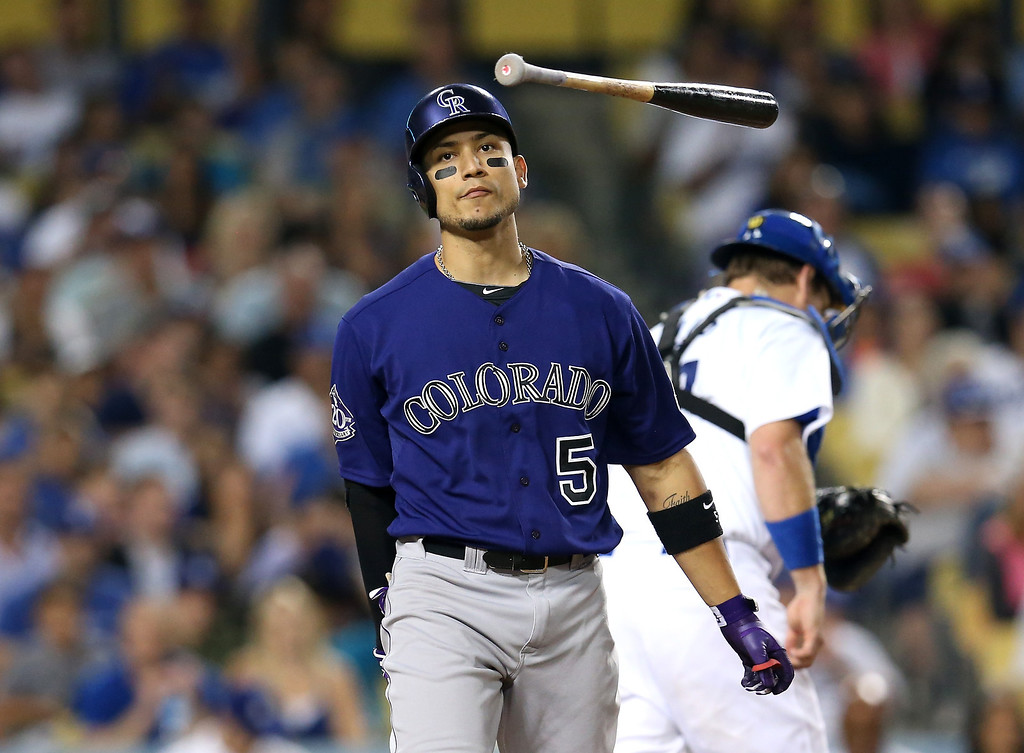 . LOS ANGELES, CA - JULY 12:  Carlos Gonzalez #5 of the Colorado Rockies flips his bat in the air after striking out to end the fifth inning against the Los Angeles Dodgers at Dodger Stadium on July 12, 2013 in Los Angeles, California.  (Photo by Stephen Dunn/Getty Images)