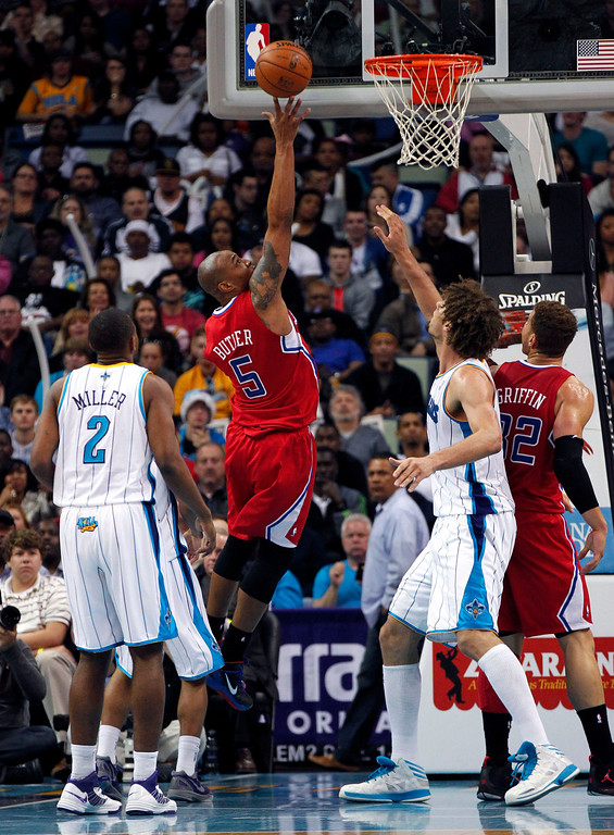 . Los Angeles Clippers small forward Caron Butler (5) drives to the basket between New Orleans Hornets small forward Darius Miller (2) and center Robin Lopez in the second half of an NBA basketball game in New Orleans, Wednesday, March 27, 2013. The Clippers won 105-91. (AP Photo/Gerald Herbert)