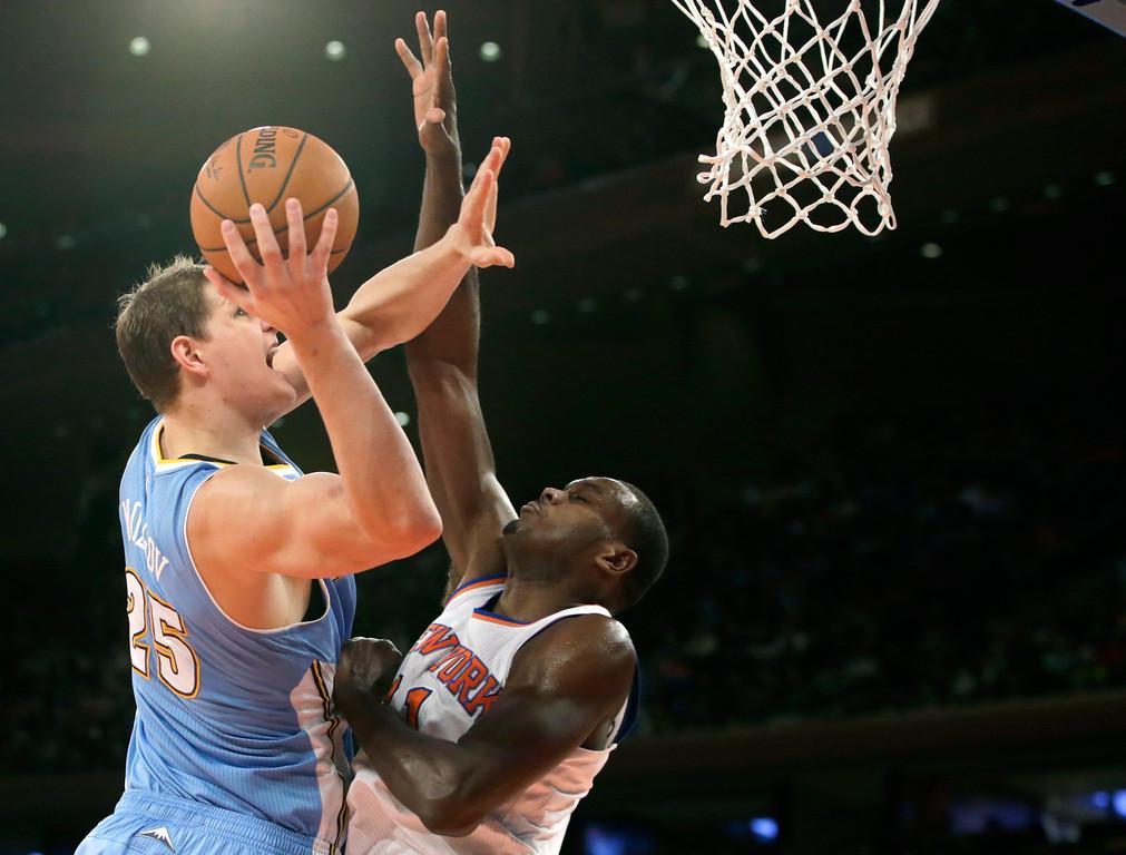 . Denver Nuggets center Timofey Mozgov (25) shoots over New York Knicks center Samuel Dalembert (11) in the first half of an NBA basketball game in New York, Sunday, Nov. 16, 2014. (AP Photo/Kathy Willens)
