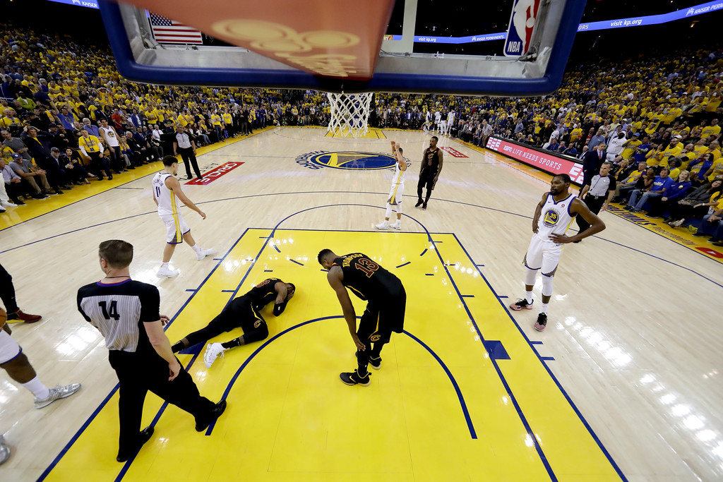 . Cleveland Cavaliers center Tristan Thompson (13) checks on forward LeBron James, on ground, during the first half of Game 1 of basketball\'s NBA Finals against the Golden State Warriors in Oakland, Calif., Thursday, May 31, 2018. (AP Photo/Marcio Jose Sanchez, pool)