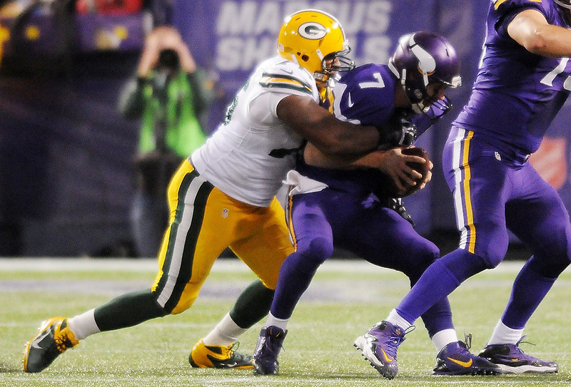 . Green Bay defensive end Mike Daniels wraps up Minnesota quarterback Christian Ponder for a 7-yard sack in the third quarter. (Pioneer Press: John Autey)
