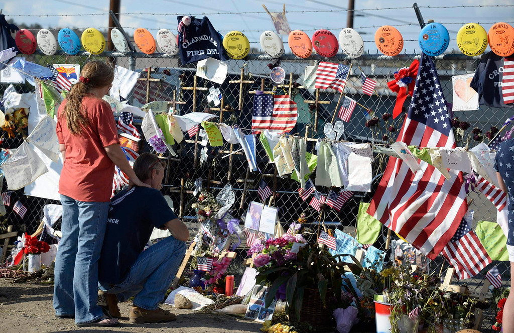 . People read memorial messages left for the fallen fighters at the memorial wall after the procession of hearses carrying the remains of the 19 members of the Granite Mountain Hotshots firefighting team, who were killed fighting the Yarnell Fire, pass by their fire station in Prescott, Arizona July 7, 2013. A solemn procession of 19 white hearses carrying the remains of firefighters killed battling an Arizona wildfire left Phoenix accompanied by police motorcycle outriders on Sunday on a final journey passing through the crew\'s hometown. REUTERS/Gene Blevins
