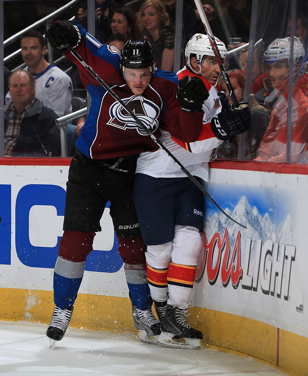 . DENVER, CO - NOVEMBER 16:  Jamie McGinn #11 of the Colorado Avalanche puts a hit on Mike Mottau #22 of the Florida Panthers at Pepsi Center on November 16, 2013 in Denver, Colorado.  (Photo by Doug Pensinger/Getty Images)