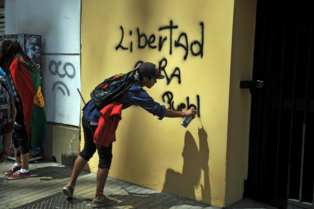 . A youngster makes a graffiti during a protest of Mapuche indigenous people for the commemoration of Columbus Day in downtown Santiago, on October 12, 2013. HECTOR RETAMAL/AFP/Getty Images