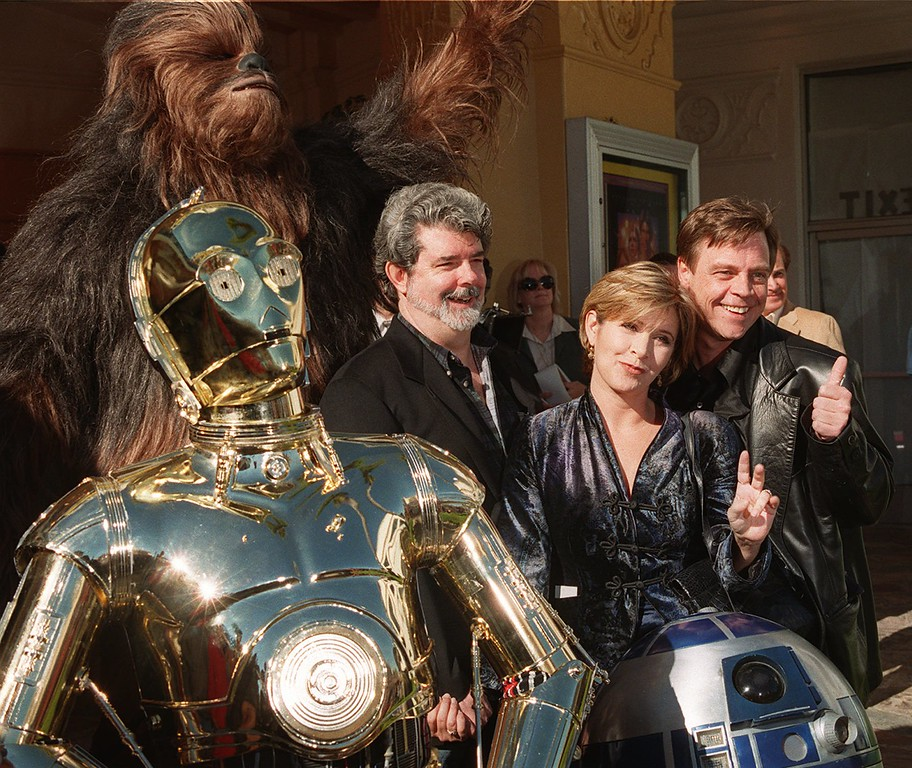 """. Characters from the film \""""Star Wars\"""" join writer and director George Lucas, left, Carrie Fisher, center, and Mark Hamill at the world premiere of \""""Star Wars Special Edition\"""" Saturday, Jan. 18, 1997, in the Westwood section of Los Angeles.  The movie  was first released 20 years ago. (AP Photo/Rene Macura)"""