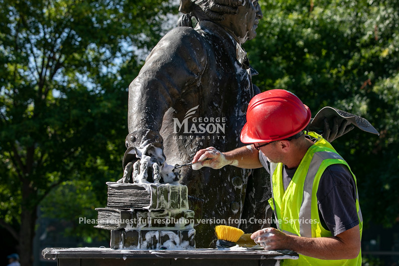 The George Mason statue is cleaned before the opening of the Enslaved People of George Mason Memorial in Wilkins Plaza. Photo by: Shelby Burgess/Strategic Communications/George Mason University