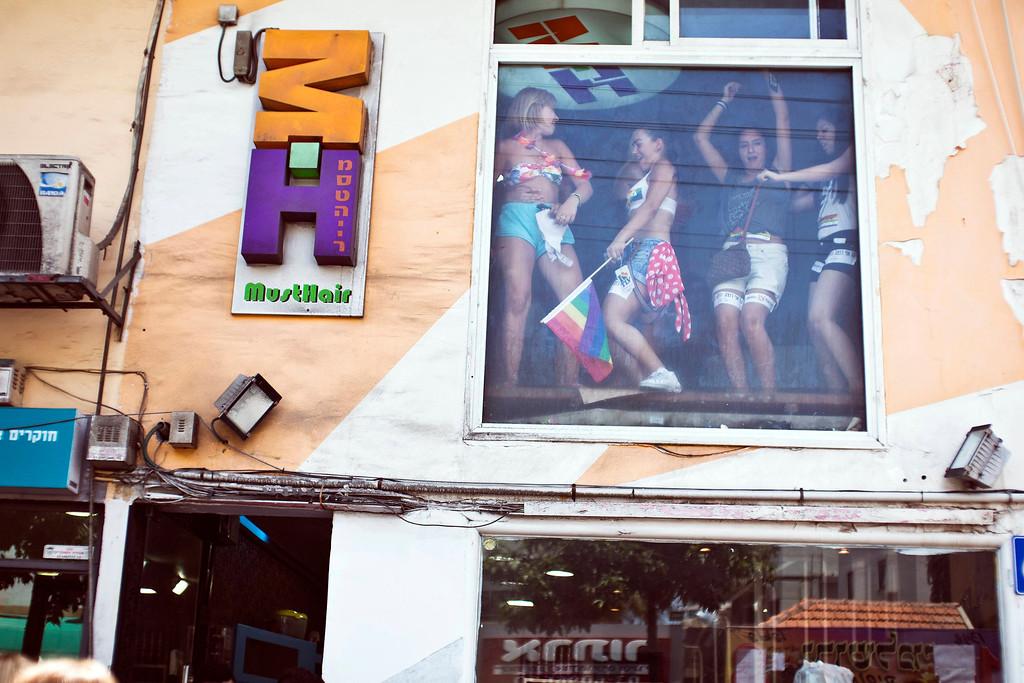 . Women dance behind a window of a shop on a street during an annual Gay Pride parade in Tel Aviv June 7, 2013. REUTERS/Nir Elias