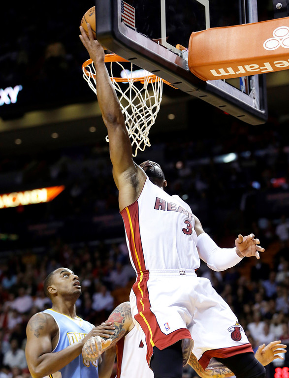 . Miami Heat guard Dwyane Wade (3) goes to the basket as Denver Nuggets forward Darrell Arthur (00) looks on during the first half of an NBA basketball game in Miami, Friday, March 14, 2014. (AP Photo/Alan Diaz)
