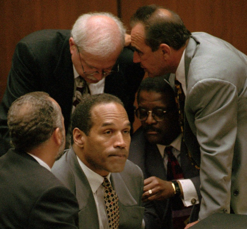 . O.J. Simpson is surrounded by his attorneys, clockwise from left, Ken Spaulding, back towards camera, Gerald Uelmen, Robert Shapiro and Johnnie Cochran Jr., as they discuss their plans for arguing the admissibility of the tapes of retired Los Angeles police detective Mark Fuhrman, Tuesday, Aug. 29, 1995 in Los Angeles. (Los Angeles Daily News file photo)