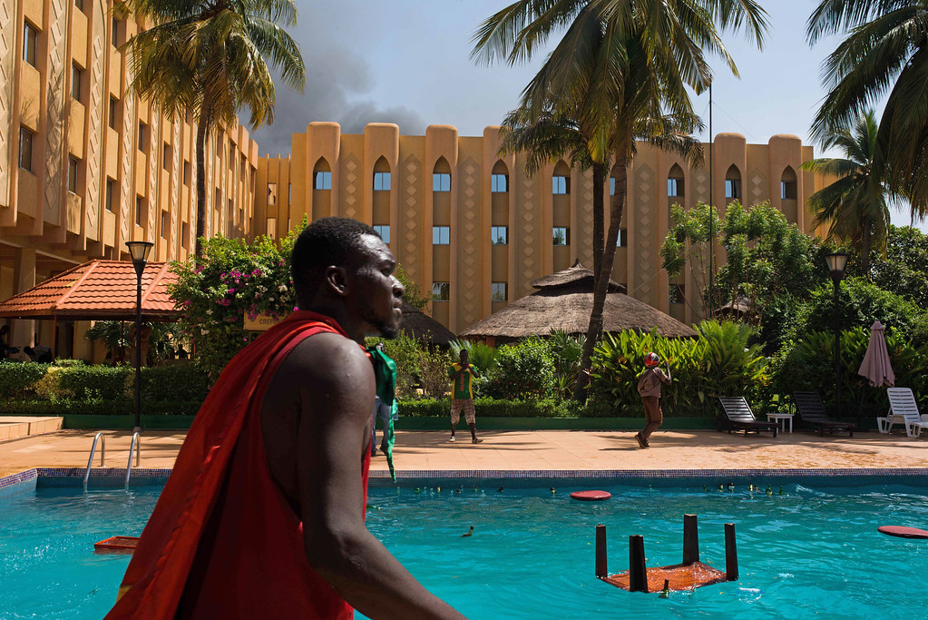 . A protestor walks past a pool as protestors ransack the Azalai Hotel in  Burkina Faso as people protest  against their longtime president  Blaise Compaore who is seeking  another term in Ouagadougou, Burkina Faso, Thursday, Oct. 30, 2014.(AP Photo/Theo Renaut)
