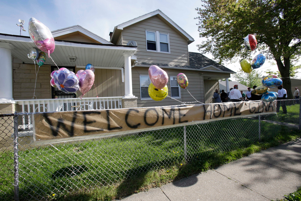 ". A ""Welcome Home Gina \"" sign hangs on a fence outside the home of Gina DeJesus  Tuesday, May 7, 2013, in Cleveland.  DeJesus, Amanda Berry and Michelle Knight, who went missing separately about a decade ago, were found in a home just south of downtown Cleveland and likely had been tied up during years of captivity, said police, who arrested three brothers. (AP Photo/Tony Dejak)"