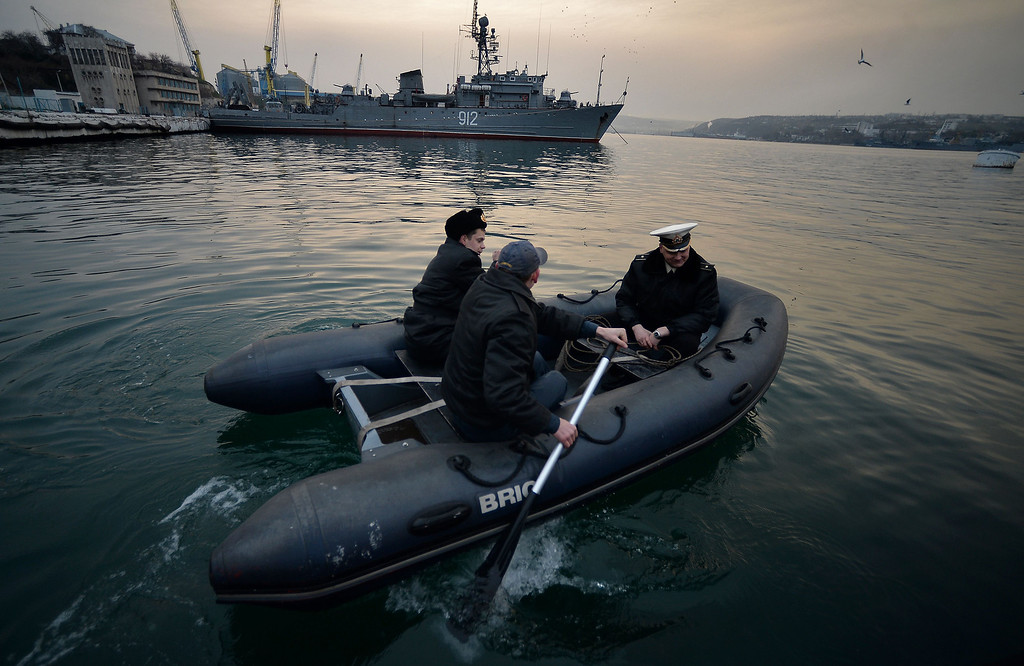 """. Officers from the Ukrainian navy ship Ternopil get on board of a boat in front of the Russian navy ship minesweeper \""""Turbinist\"""" anchored at the harbor of Sevastopol on March 11, 2014.  Lawmakers on the flashpoint Crimean peninsula voted on March 11 for independence from Ukraine ahead of a referendum on joining Russia while Washington rebuffed talks with Moscow in one of their fiercest clashes since the Cold War. The strategic region\'s self-declared rulers are recruiting volunteers to fight Ukrainian soldiers while Russia\'s parliament on March 11 prepared legislation that would simplify the Kremlin\'s annexation of Crimea after the weekend\'s vote.  FILIPPO MONTEFORTE/AFP/Getty Images"""