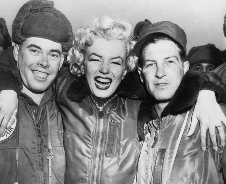 . Marilyn Monroe put her arms around Pfc. John Fenesy, left, of Caldwell, New Jersey and Cpl. Dick Armstrong, right, of Williston Park, New York, at the 3rd division airstrip during her four day tour of Korea, February 19, 1954. (AP Photo)