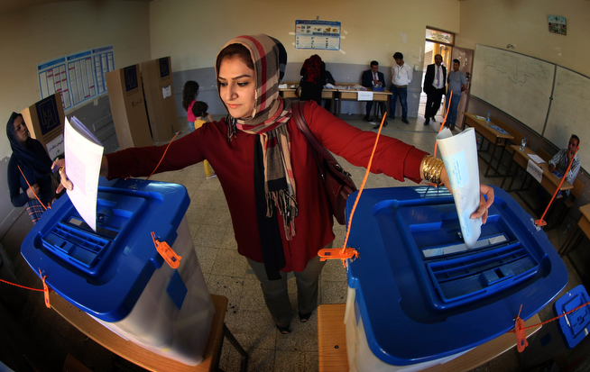 """. An Iraqi woman casts her vote in Iraq\'s parliamentary election (ballot-L) and in a postponed Kurdish regional election (ballot-R) in the Iraqi city of Kirkuk on April 30, 2014. Iraqis defied a rash of attacks that killed 14 people and voted in the first general election since US troops withdrew, with Prime Minister Nuri al-Maliki proclaiming \""""certain\"""" victory. (MARWAN IBRAHIM/AFP/Getty Images)"""
