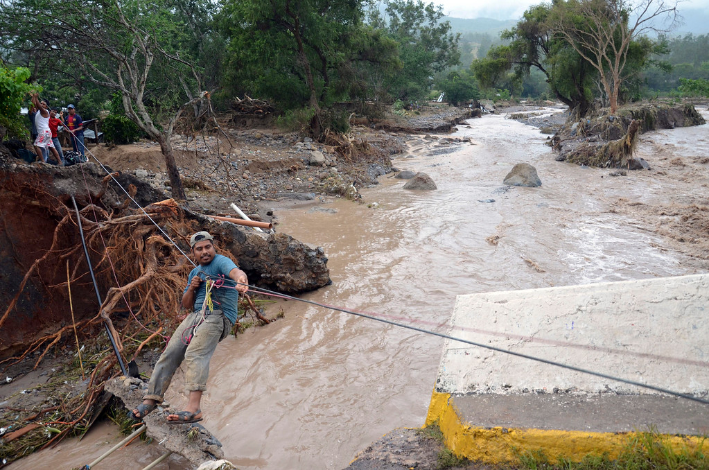 . A man uses a makeshift zip line to cross a river after a bridge collapsed under the force of the rains caused by Tropical Storm Manuel near the town of Petaquillas, Mexico, Wednesday, Sept. 18, 2013. The death toll from devastating twin storms climbed to 80 on Wednesday as isolated areas reported to the outside world. Mexican officials said that a massive landslide in the mountains north of Acapulco could drive the number of confirmed dead even higher. (AP Photo/Alejandrino Gonzalez)