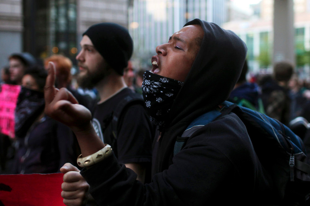 . A woman gestures at Seattle Police Department officers during May Day demonstrations in Seattle, Washington May 1, 2013. Protesters clashed with police in Seattle on Wednesday as a May Day rally that began peacefully turned violent after dark, with demonstrators hurling objects at officers who responded by firing flash-bang grenades and pepper spray.  REUTERS/Matt Mills McKnight