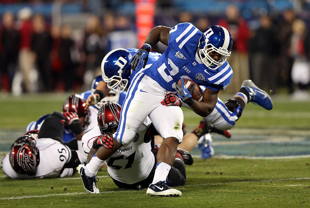 Description of . Greg Blair #51 of the Cincinnati Bearcats tackles Juwan Thompson #23 of the Duke Blue Devils during their game at Bank of America Stadium on December 27, 2012 in Charlotte, North Carolina.  (Photo by Streeter Lecka/Getty Images)