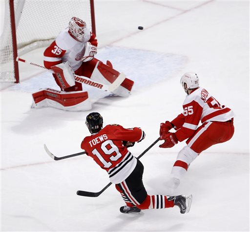 . Detroit Red Wings goalie Jimmy Howard (35) makes a save on a shot by Chicago Blackhawks center Jonathan Toews (19) as Niklas Kronwall (55) also defends during the first period of an NHL hockey game Wednesday, Feb. 18, 2015, in Chicago. (AP Photo/Charles Rex Arbogast)