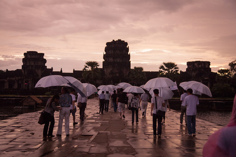 Tourists with matching white umbrellas walking to Angkor Wat at sunrise.