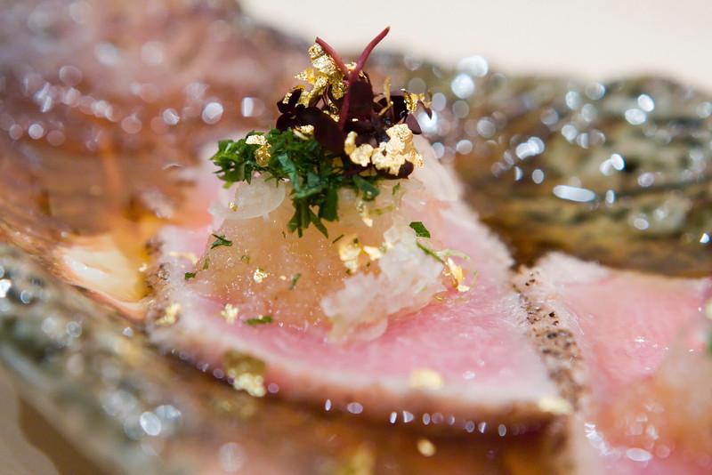 Course #3.  Tuna tatami - seared tuna with radish, garnish, and gold flakes.