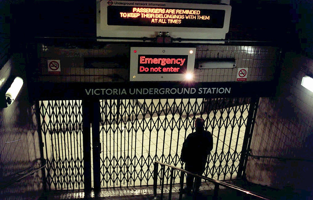 Description of . A lone person stands in front of the locked gates at Victoria Underground station in London Wednesday evening November 20, 1996, after a system-wide power cut meant that thousands of passengers were stranded on subway trains. London Underground was planning an emergency regeneration of the system, to allow all trains to reach stations. (AP Photo/Rebecca Naden/PA)