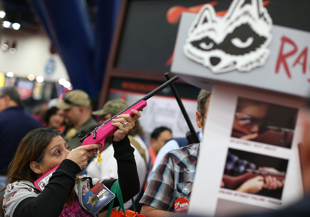 ". HOUSTON, TX - MAY 04:  An attendee inspects a Savage 22 Single Shot ""Rascal\"" youth model rifle during the 2013 NRA Annual Meeting and Exhibits at the George R. Brown Convention Center on May 4, 2013 in Houston, Texas.  More than 70,000 peope are expected to attend the NRA\'s 3-day annual meeting that features nearly 550 exhibitors, gun trade show and a political rally. The Show runs from May 3-5.  (Photo by Justin Sullivan/Getty Images)"