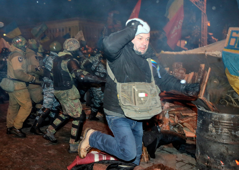 . An Pro-European Union activist runs during clash with  riot police  on the Independence Square in Kiev, Ukraine, Wednesday, Dec. 11, 2013. Security forces clashed with protesters as they began tearing down opposition barricades and tents set up in the center of the Ukrainian capital early Wednesday, in an escalation of the weeks-long standoff threatening the leadership of President Viktor Yanukovych.  (AP Photo/Efrem Lukatsky)