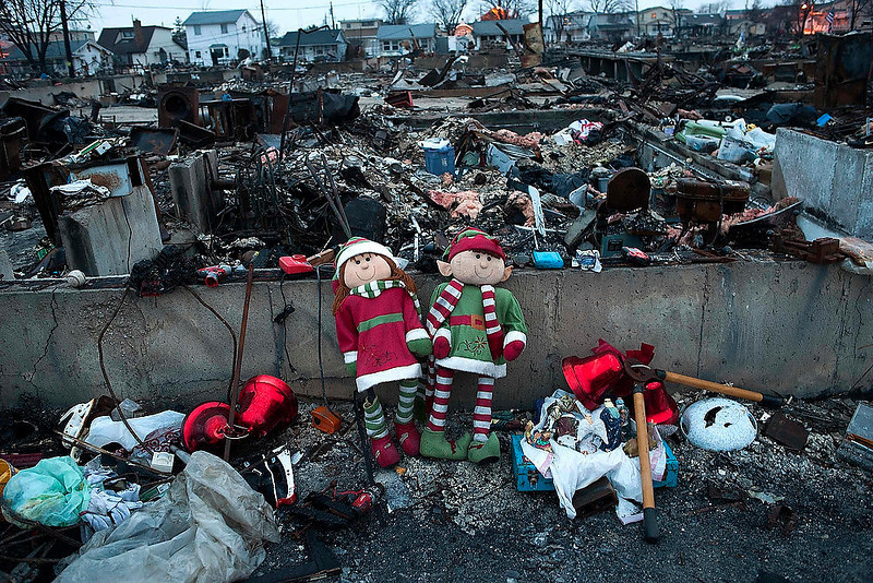 . Christmas ornaments sit amongst the remains of homes destroyed by fire during Hurricane Sandy in the Breezy Point area of New York\'s borough of Queens, on December 25, 2012.   REUTERS/Keith Bedford