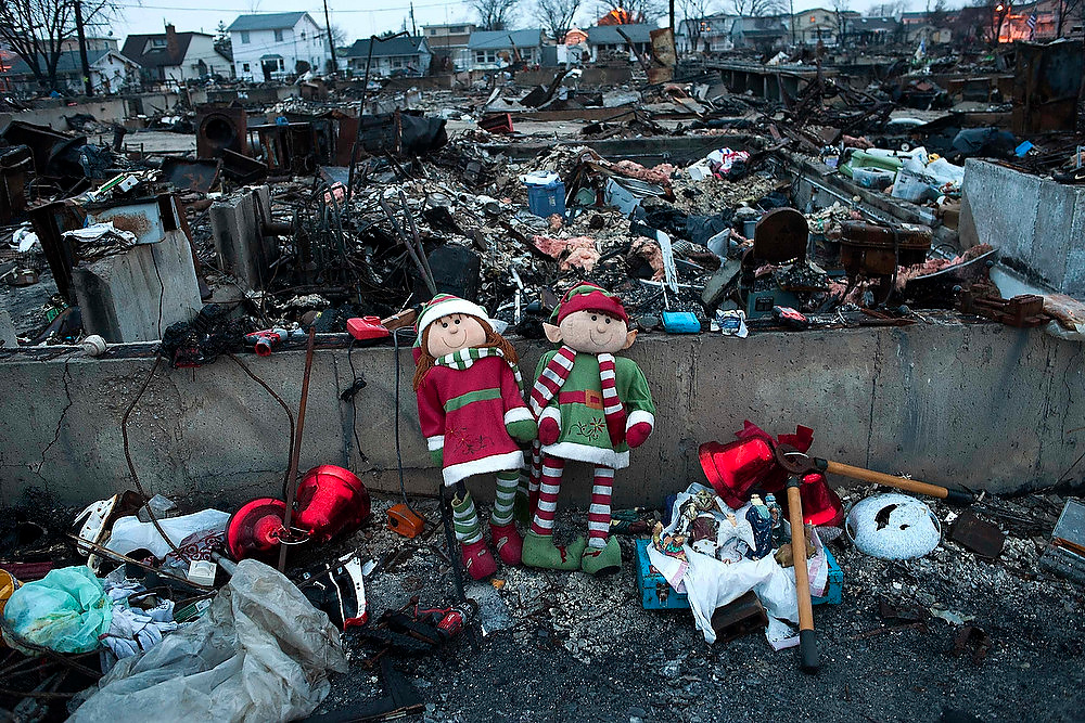 Description of . Christmas ornaments sit amongst the remains of homes destroyed by fire during Hurricane Sandy in the Breezy Point area of New York's borough of Queens, on December 25, 2012.   REUTERS/Keith Bedford