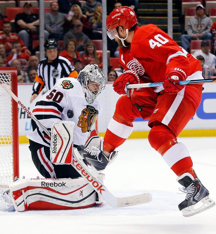 . Detroit Red Wings left wing Henrik Zetterberg (40), jumps as Chicago Blackhawks goalie Corey Crawford (50) stops a shot in the second period of an NHL hockey game in Detroit, Friday, Nov. 14, 2014. (AP Photo/Paul Sancya)
