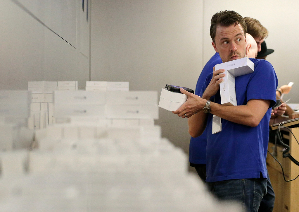 . An Apple store employee pulls iPhone 6s and 6 Pluses that were pre-ordered from a stack to give to waiting customers, Friday, Sept. 19, 2014,  in New York. The highly anticipated iPhone 6 and iPhone 6 Plus are being released in stores today. (AP Photo/Julie Jacobson)