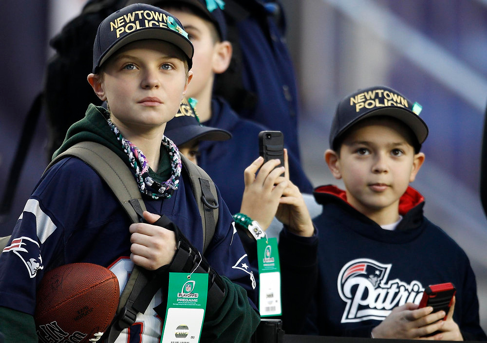 Description of . Young fans wear Newtown Connecticut Police department hats in the stands before the NFL AFC Divisional playoff football game between the New England Patriots and the Houston Texans in Foxborough, Massachusets January 13, 2013. REUTERS/Jessica Rinaldi