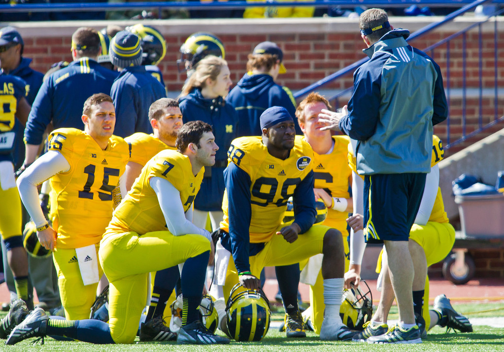 . Michigan quarterback Shane Morris (7), quarterback Devin Gardner (98), and fellow quarterbacks kneel in front of offensive coordinator Doug Nussmeier as he addresses them, during the football team\'s annual spring game, Saturday, April 5, 2014, in Ann Arbor, Mich. (AP Photo/Tony Ding)