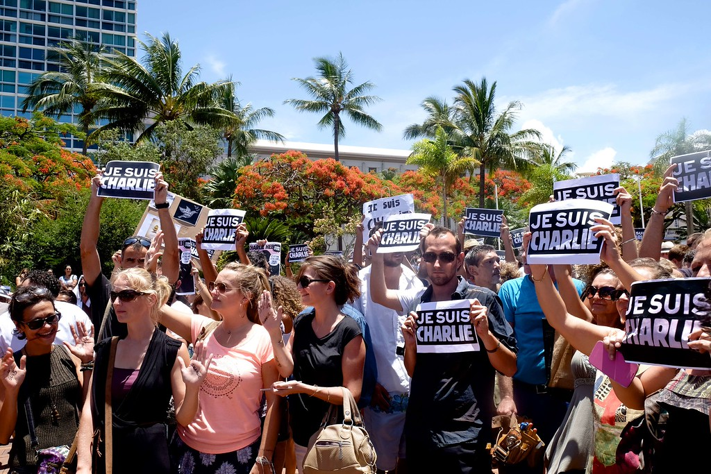 ". People hold up signs reading ""Je suis Charlie\"" (I am Charlie) during a gathering at the Place des Cocotiers, in Noumea, New Caledonia, on January 8, 2015, to pay homage to the victims of an attack on January 7 by armed gunmen on the offices of the French satirical weekly Charlie Hebdo which left 12 dead. France\'s prime minister said on January 8 that several people had been detained in the hunt for two brothers suspected of gunning down 12 people in an Islamist assault on a satirical weekly that shocked the country. AFP PHOTO / THEO  ROUBY/AFP/Getty Images"