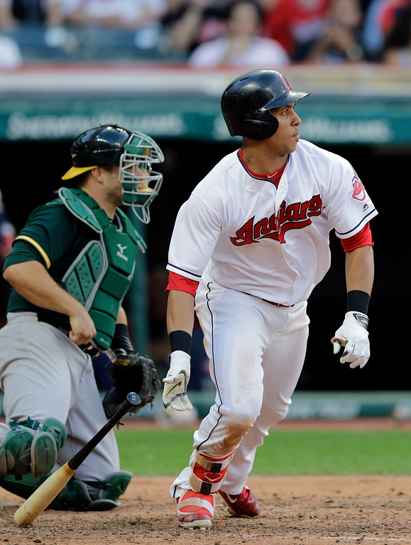 . Cleveland Indians\' Michael Brantley watches his ball after hitting an RBI-single off Oakland Athletics starting pitcher Sonny Gray in the fifth inning of a baseball game, Tuesday, May 30, 2017, in Cleveland. Francisco Lindor scored on the play. Catcher Josh Phegley watches. (AP Photo/Tony Dejak)